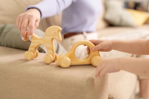 Руки молодой женщины и маленького мальчика с деревянной лошадью и автомобилем, играющих вместе на диване, оставаясь дома во время карантина