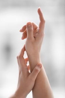 Руки молодой женщины, применяя крем дома