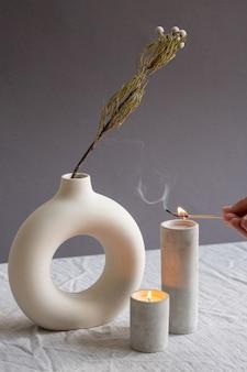 花瓶のそばに立っている白い手作りのセラミックガラスの2つの芳香キャンドルの1つに燃えるマッチを保持している若い女性の手