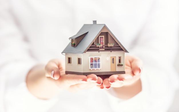 Руки молодой женщины, держащей модельный дом, страхование недвижимости и банковское дело.