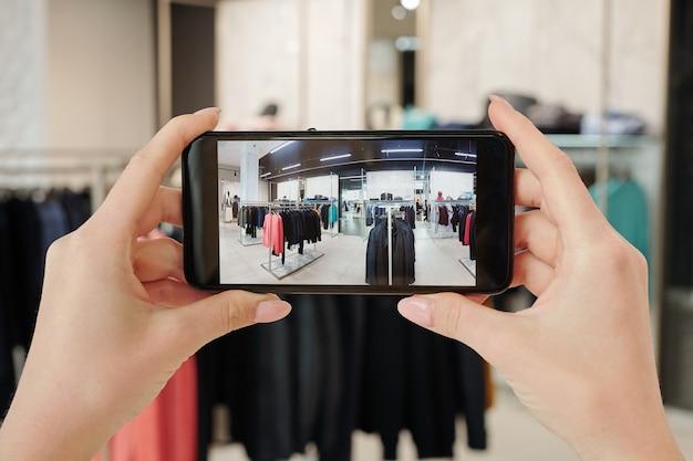 スマートフォンを保持していると服のラックと現代的なブティックのインテリアの写真を撮る若い女性の手