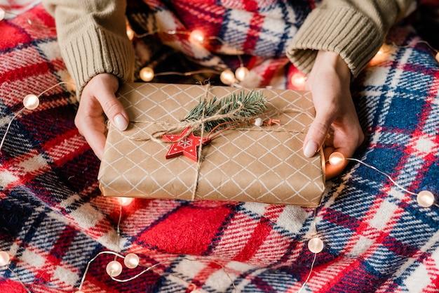 市松模様のウールの格子縞と輝く花輪の上に赤い星と針葉樹の包まれたギフトボックスを保持している若い女性の手