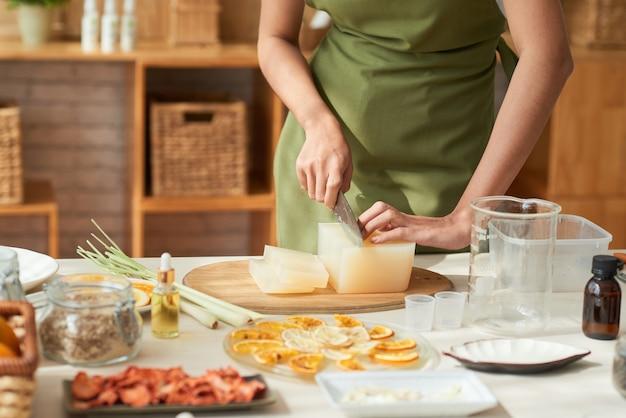 집에서 클렌징 바를 만들 때 비누 베이스를 자르는 앞치마를 입은 젊은 여성의 손