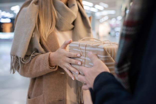 彼の前に立っている間彼女の夫またはボーイフレンドからギフトボックスを取ってベージュのウールのコートを着た若い女性の手