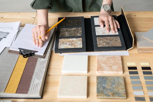Руки молодой женщины делают заметки на бумаге, выбирая образец панели из коллекции во время работы над новым заказом