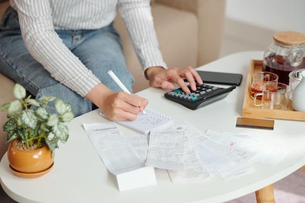月々の経費を管理している若い女性の手、彼女は請求書をチェックし、フィグレスを書き留めています