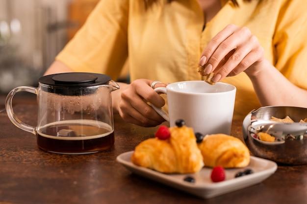 Руки молодой женщины кладут два кусочка тростникового сахара в чашку со свежим чаем во время завтрака за столом на кухне