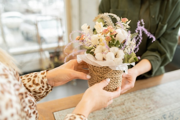 Руки молодой женщины принимают небольшую корзину с цветочным букетом во время посещения цветочного магазина, чтобы купить цветы для своей подруги или матери