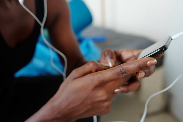 トレーニング用の音楽を選択するときにソーシャルメディア上のアプリケーションを使用して若い女性の手