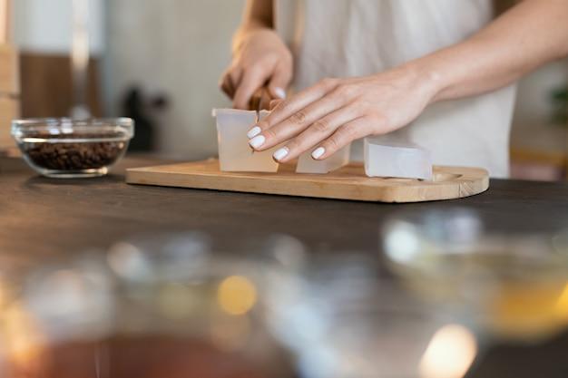 Руки молодой женщины с ножом, отрезающим кусок твердой мыльной массы на деревянной доске, делая дома натуральные косметические продукты