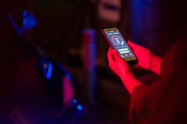 Руки молодой женщины с умным зарядным устройством на экране смартфона