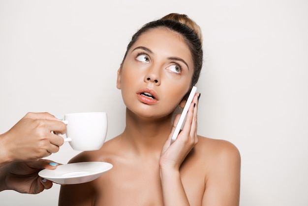 Hands offering cup of coffee to woman speaking on phone