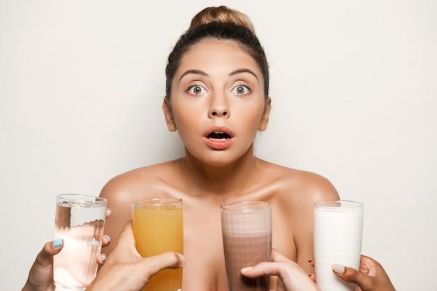 Hands offering water, juice, coffee or milk to beautiful woman