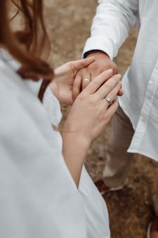 結婚指輪のある新婚夫婦の手と結婚指輪のある新婚夫婦のウェディングブーケ