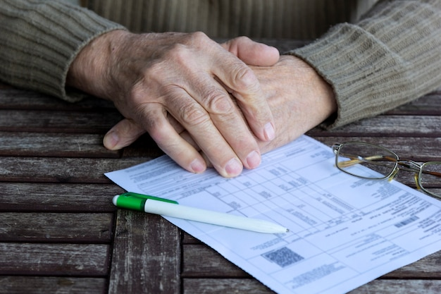 Hands of old senior man fills in utility bills on wooden table.