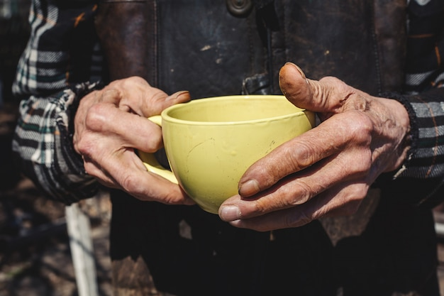 Hands of old senior with cup of tea