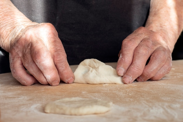 The hands of an old woman are making pies out of dough