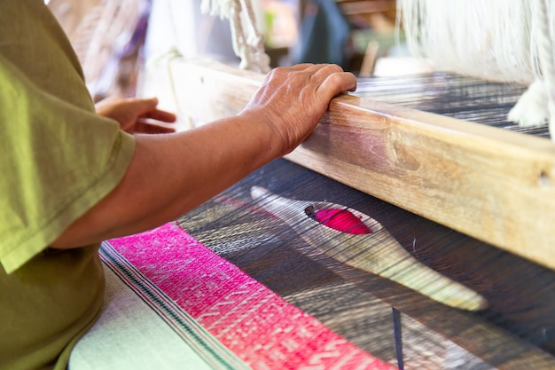 The hands of old woman weaving, the ancient weaving method.