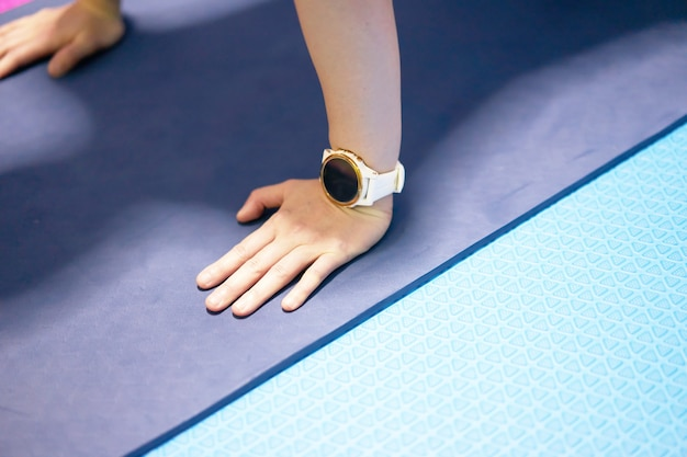 トレーニングエクササイズフィットネスセッション、ハイアングルビューでのスポーツモニターウォッチ付きマットフロアのハンズオン