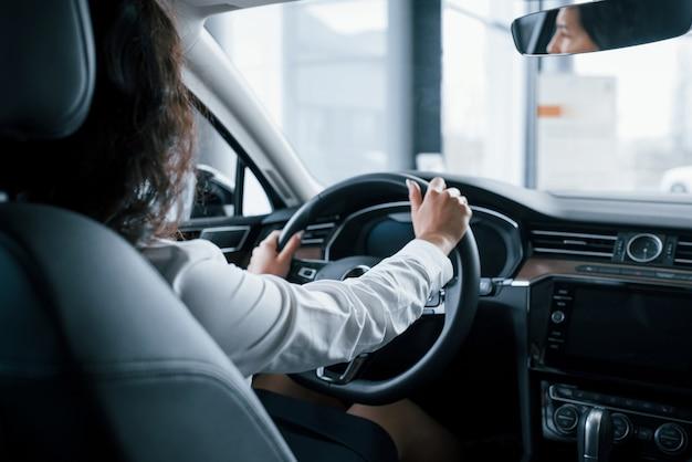 ステアリングホイールに手。自動車サロンで彼女の新しい車をしようとしている美しい女性実業家