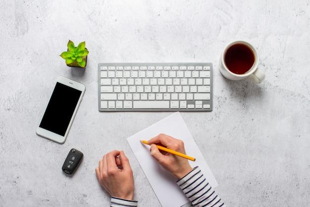 キーボード、車のキー、一杯のコーヒー、空白の紙、鉛筆、コンクリートの背景に部屋の花の手。