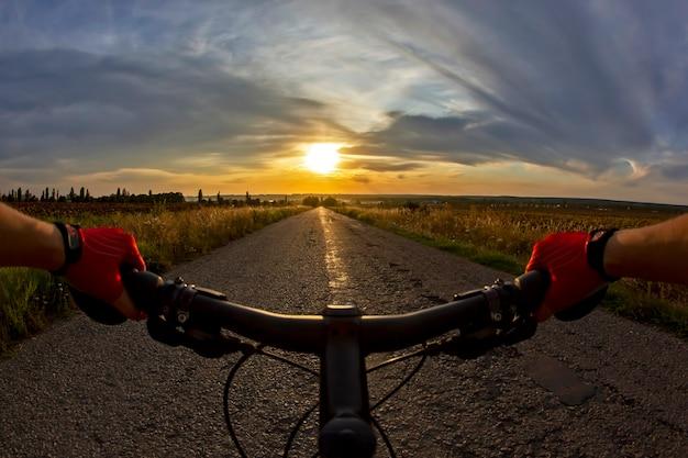 일몰을 향해 도로에서 자전거 타는 사람을 타고 스티어링 휠에 손