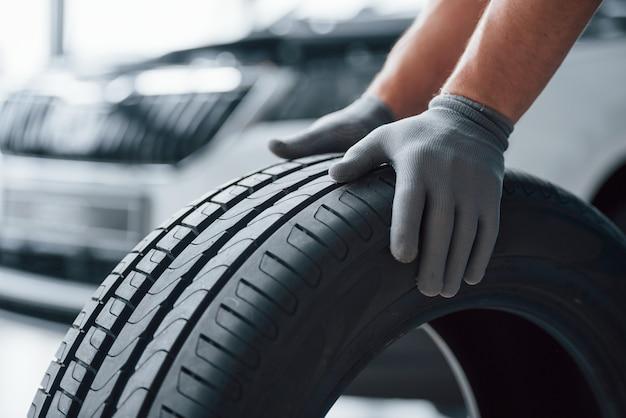 Только руки. механик держит шину в ремонтном гараже. замена зимней и летней резины
