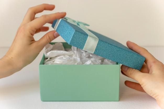 Руки открывают красивую подарочную коробку на свете