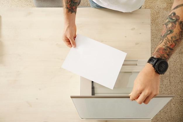 손에 스캐너 트레이를 열고 흰색 나무 테이블, 평면도에 고립 된 가정용 다기능 전자 장치에 문서를 스캔하기 위해 종이를 넣어