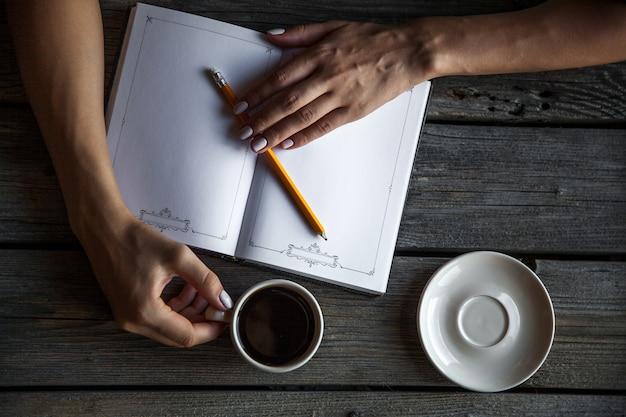 手は空白のカタログ、雑誌、コーヒーと木製のテーブルの上の本を開きます