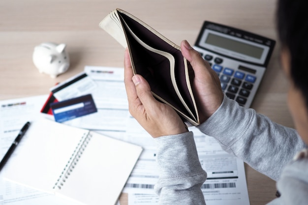 Hands open the empty purse after calculating the cost from the credit card and bill. debt concept