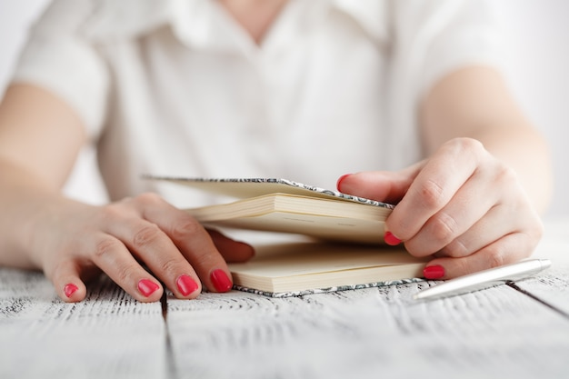 Hands open notebook on wood table