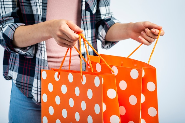 Hands opening polka dot shopping bags