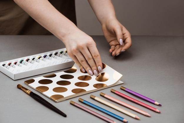 Руки открывают альбом с масляными красками и карандашами на сером столе