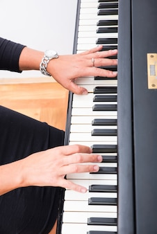 Hands os a classical musician woman playing on piano.