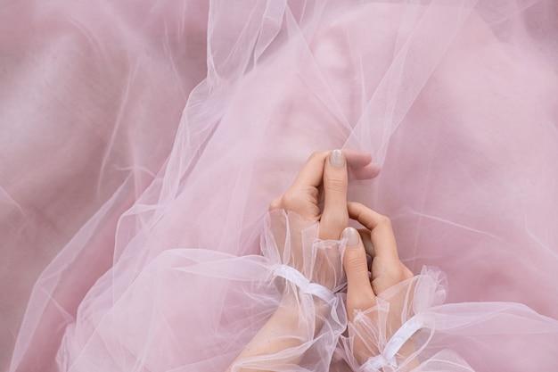 Руки над розовым элегантным платьем позируют.