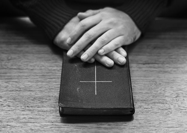 나무 테이블에 성경에 손
