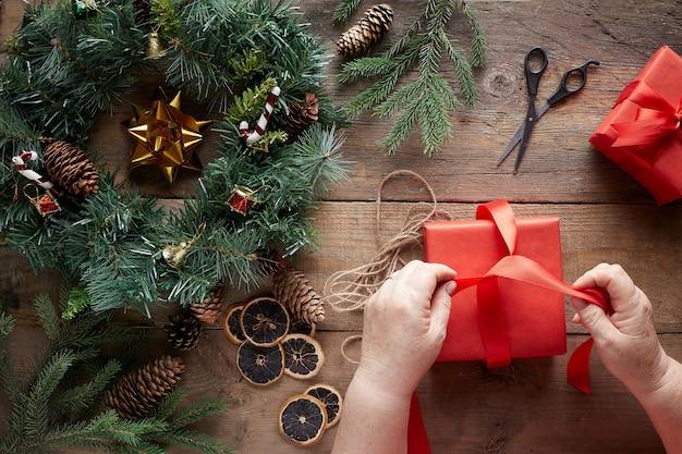 Передает рождественский венок и представляет на деревянном фоне