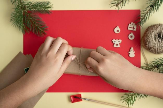 赤い背景に新年やクリスマスのギフトボックスを梱包する手メリークリスマス詐欺