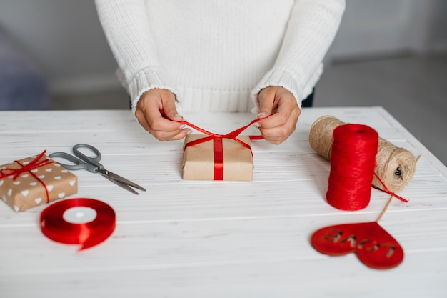 Hands packing gift with red ribbon on table