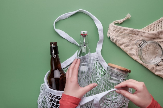 Hands packing glass bottles and jar in mesh bag