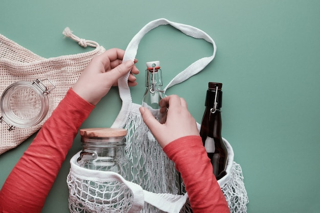 Hands packing glass bottles and jar in mesh bag.