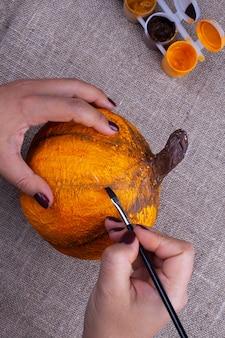 手はハロウィーンのためにオレンジ色の自家製張り子のカボチャをペイントします、子供のための趣味