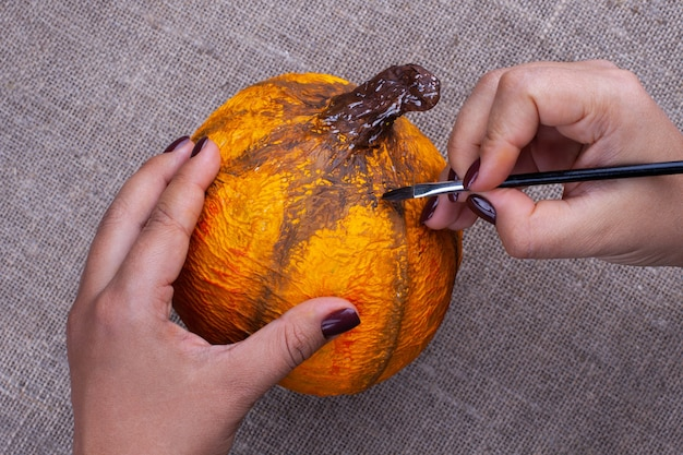 手はハロウィーンのための張り子からガッシュオレンジ色のクラフトカボチャでブラシでペイントします