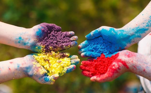 Руки / ладони молодых людей, покрытые фиолетовыми, желтыми, красными, синими цветами фестиваля холи изолированы