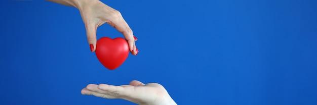 Hands pass red heart heart disease concept
