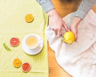 Hands peeling lemon citron in bright surroundings
