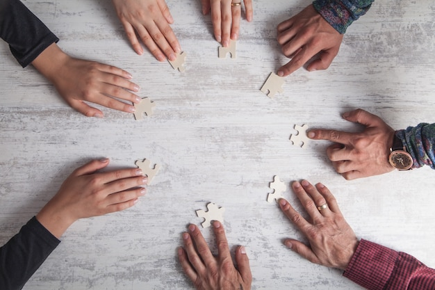 Hands of people holding jigsaw puzzle. partnership, success, teamwork