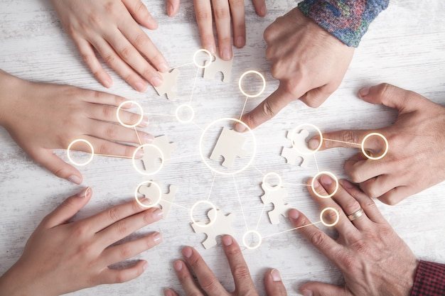 Hands of people holding jigsaw puzzle.
