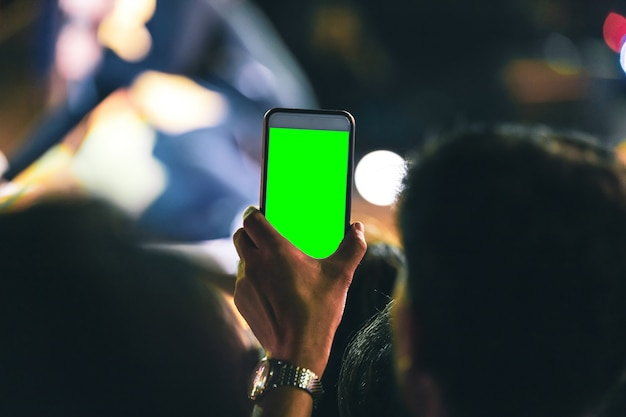 Hands of people holding mobile smart phone with green screen recording and taking a picture at music concert